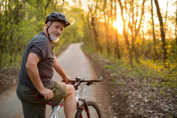 image of an older man exercising outdoors on a bike